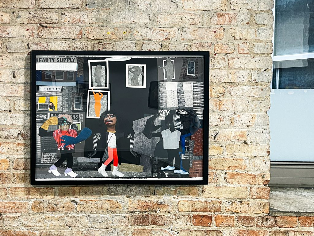"""Image: An installation view of """"Girls on the Avenue"""" by SHAN Wallace. Digital collage 30 x 24 x 1.75 inches (framed in black) (76.2 x 61 x 4.45 cm), 2021. The collage shows several figures in a city setting. Courtesy of the artist and FLXST Contemporary."""