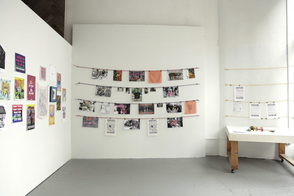 Image: Gallery walls with printed materials hung from strings affixed to the wall. Image courtesy of Silvia Inés Gonzalez.