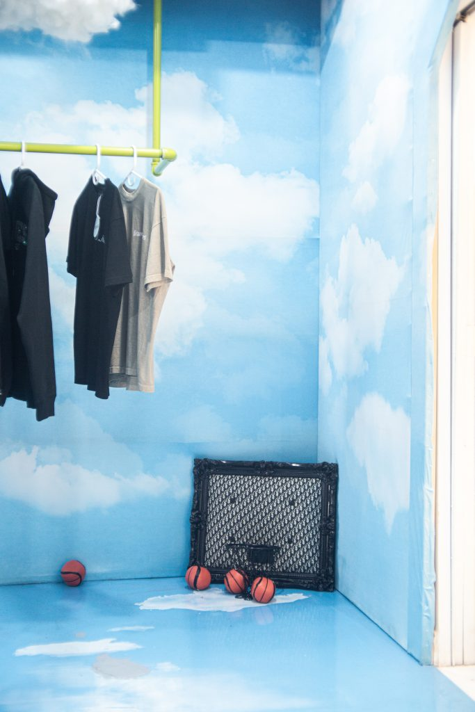 Image: A pop-up at Congruent Space featuring Hoop Dreams Studio. The walls and floor are covering by a blue sky and clouds. Basketballs and a basket and backboard sit on the ground. Clothes hang on a rack to the left. Photo by Dally Dew Drop.