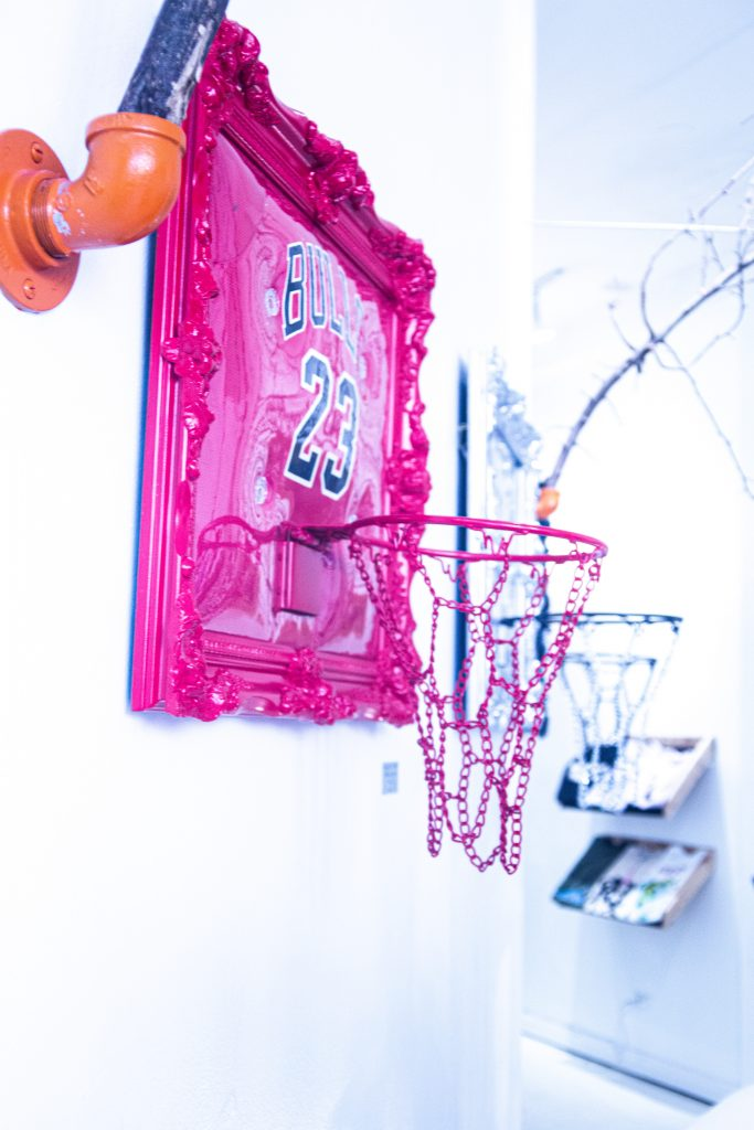 Image: A pop-up at Congruent Space featuring Hoop Dreams Studio. A magenta basketball hoop and headboard hangs on the white wall, with additional hoops in the background. Photo by Dally Dew Drop.