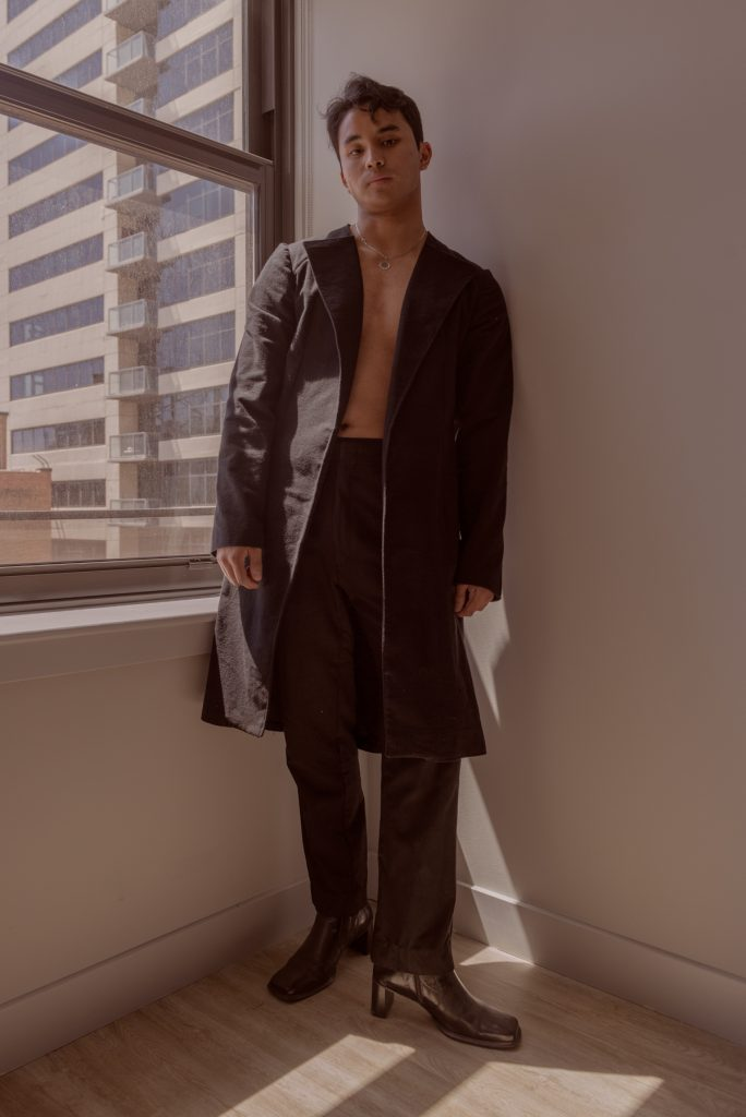 Image: Sam Fissell stands in front of a window while wearing a dark-colored, collared jacket. The jacket is open, revealing a silver neckless. The trousers are also dark and he is wearing black, healed shoes. Photo by Ryan Edmund Thiel.