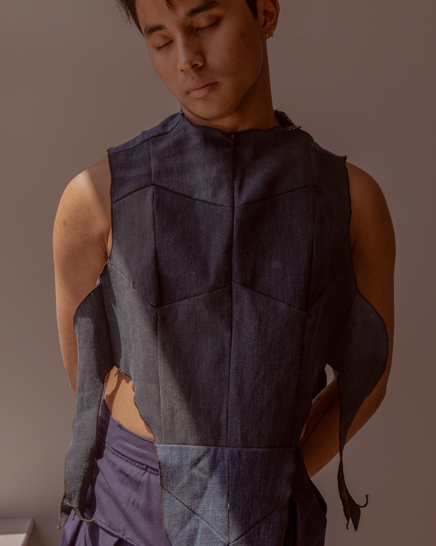 Image: Sam Fissell has one arm behind his back while looking down. He is wearing a dark-colored garment with ripped detailing and a geometric-like pattern. Photo by Ryan Edmund Thiel.