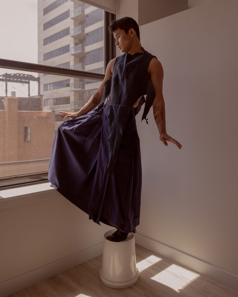 Image: Sam Fissell stands in front of a window and a white wall while posing with his arms slightly out and with one leg bent upwards while standing on a white bucket. He is wearing a dark, violet/blue garment that has ripped details towards the top and spreads out into a skirt shape towards the bottom. Photo by Ryan Edmund Thiel.