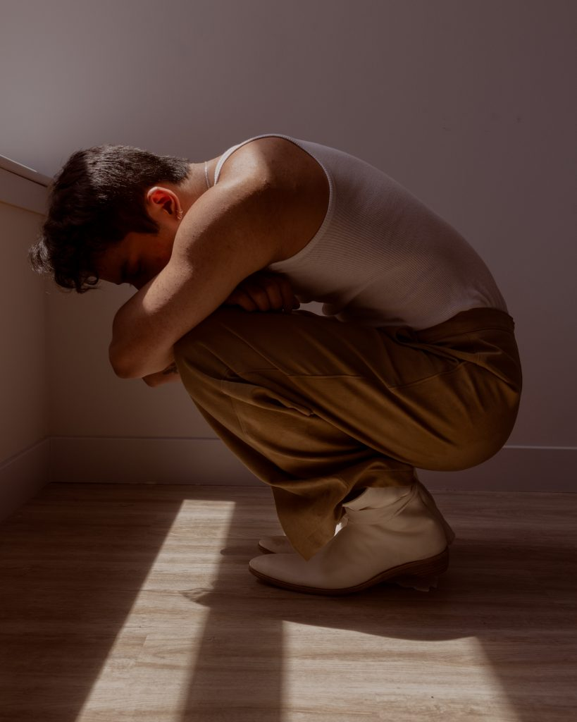 Image: Sam Fissell crouches while wearing tan trousers, a white tank top, a silver necklace, and white shoes with a white cloth tied around the ankle. Photo by Ryan Edmund Thiel.