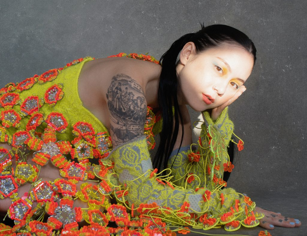 Image: A portrait of Michelle Zauner by Tonje Thilesen. Zauner crouches down with her head in her hand while looking at the viewer. She wears a brightly colored outfit that is textured with green and orange. She wears yellow make up and a spot of sunlight hits her face.