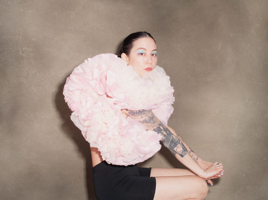 Image: A portrait of Michelle Zauner by Tonje Thilesen. Zauner sits while looking at the camera. She is wearing blue eye shadow, black shorts, and a pink, puffy top.