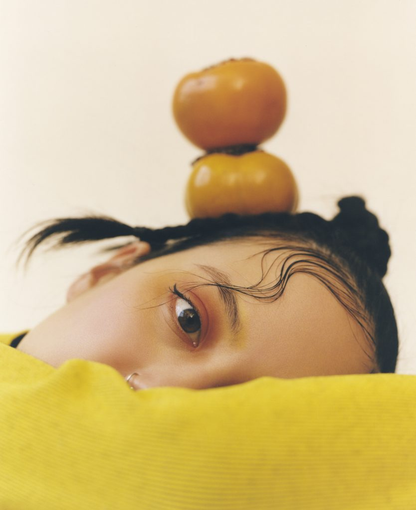 Image: A portrait of Michelle Zauner by Peter Ash Lee. Zauner faces the camera with her head on her arm. She wears yellow while wearing yellow and orange make up. An orange vegetable sits on her head.
