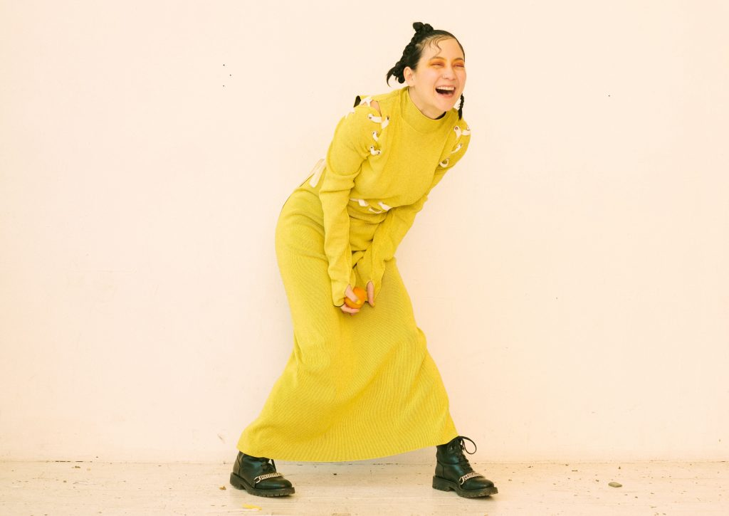 Image: A portrait of Michelle Zauner by Peter Ash Lee. Zander stands in front of a white wall while wearing a bright yellow dress and black boots. Her hair is in braids and she wears orange eye shadow while laughing.
