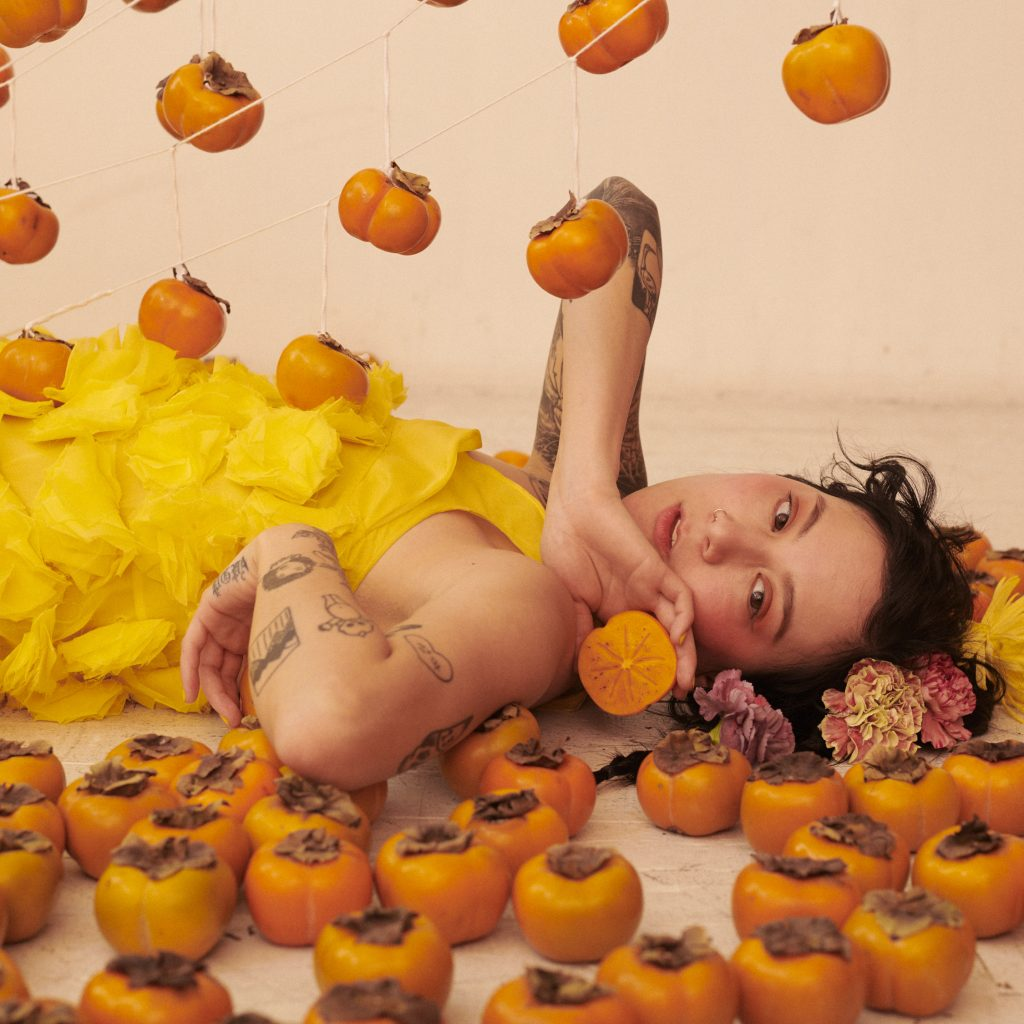 Image: A portrait of Michelle Zauner by Peter Ash Lee. Zander lays on the floor surrounded by orange vegetables suspended above her and laying around her. She holds one in her hand with flowers around her head.