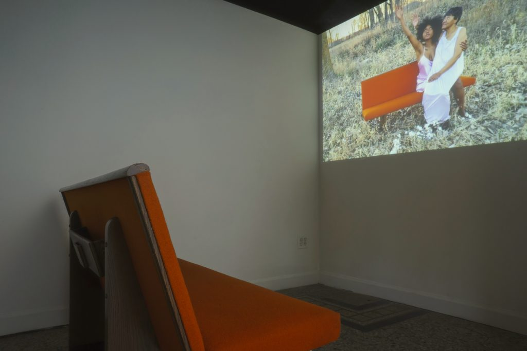 """Image: A view of a video installation in the exhibition """"Dreamscapes: Imaginings of a Black Pastoral"""" at Roots and Culture. The video shows two Black people sitting on an orange couch in in the grass. Photo by Colectivo Multipolar."""