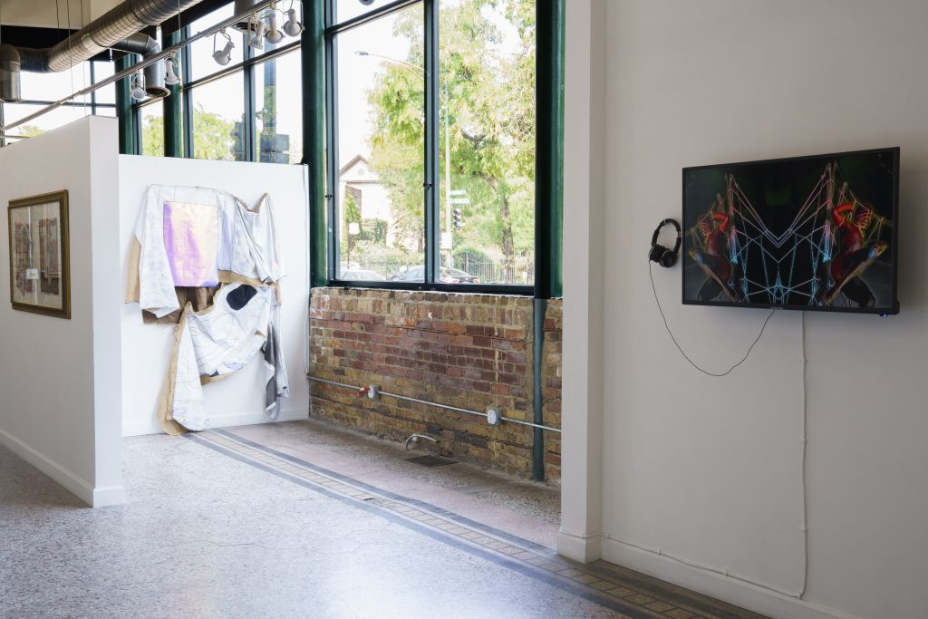 """Image: A view of """"Dreamscapes: Imaginings of a Black Pastoral"""" at Roots and Culture. On the right side is a video piece installed on a screen on the wall. On the left are several pieces on view, one being a framed collage and the other being a large textile piece. Photo by Colectivo Multipolar."""