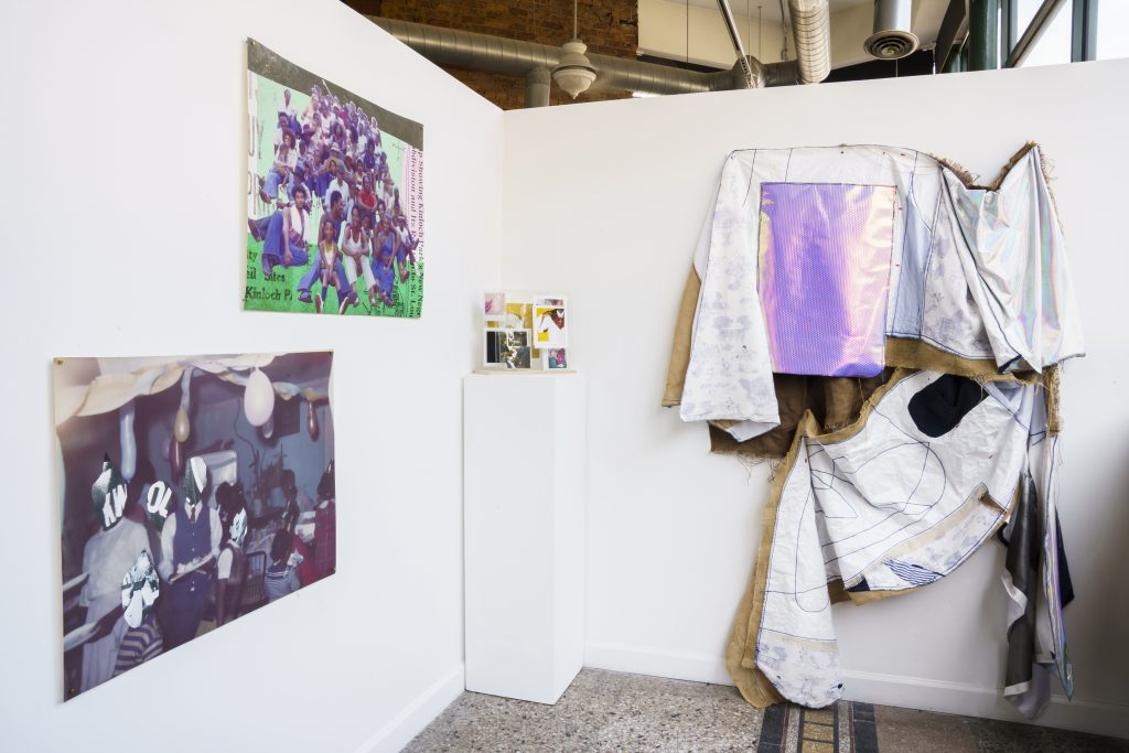 """Image: A view of """"Dreamscapes: Imaginings of a Black Pastoral"""" at Roots and Culture. On the right side is a large textile piece, and on the left are three photographic pieces on display. Photo by Colectivo Multipolar."""