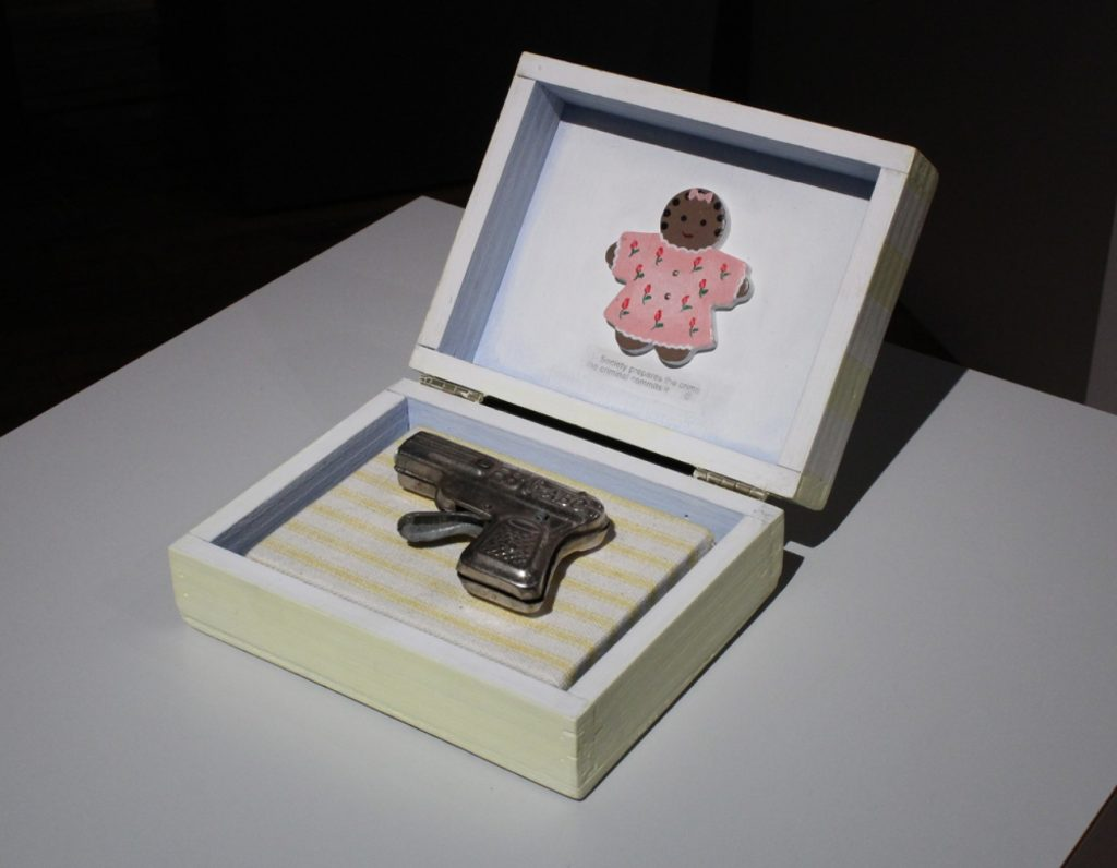 """Image: Renée Stout, """"Baby's First Gun,"""" 1998. Mixed media and toy gun. An open box displays a cap gun and a gingerbread girl cutout with text that reads: """"Society prepares the crime, the criminal commits it."""" Courtesy of Belger Arts Center, Kansas City, MO."""