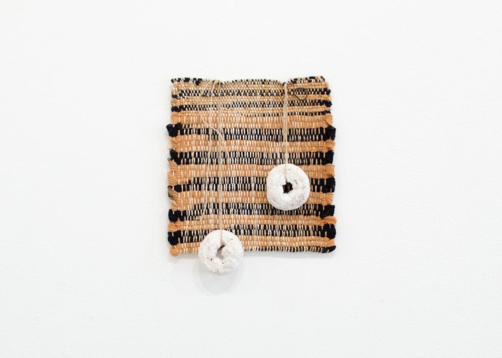 """Image: KG, """"Cleanup Time,"""" 2021. Bleach soaked cotton stripes strung with Donettes stabbed through with this old dog's nose, 7"""" x 9"""". A nearly square textile piece with beige and black stripes hangs on a while with two white donuts hanging from it. Image courtesy of LVL3."""