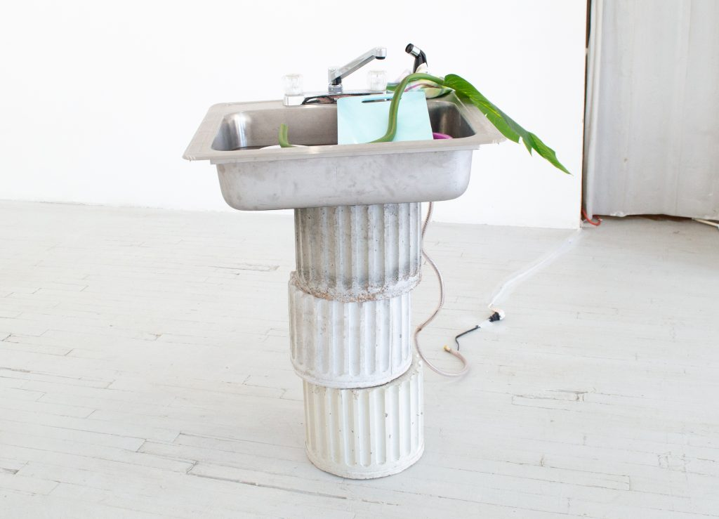"""Image: Rachel Youn, """"Prune,"""" 2021. Artificial leaf, pump, sink, dishes, dish cloth, concrete, 38"""" x 25"""" x 22"""". There sections of a a concrete pillar are stacked in a gallery with a sink on top. In the sink are various items, including a large artificial leaf. Image courtesy of LVL3."""