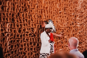 A photo of Shimmy LaRoux, a member of the usher board for The People's Church, standing in front of a brown wall covered in paper bags and an audience, wearing all white with red gloves and palms together in front of her in prayer. Photo by Candice Majors.