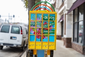 Urooj Shakeel's Truck Art Meets Little Free Library, installation view along Devon Avenue in Chicago. The image shows a small, yellow truck sculpture with bright multicolored images painted on each side, held up by a bright blue stake in the ground. Photo by Mark Blanchard.